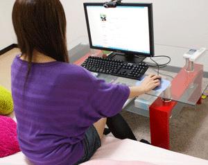 パソコンでチャットをする女性の画像